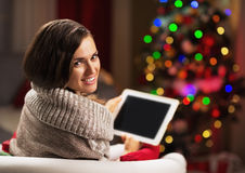 Happy young woman with tablet pc in front of christmas tree Stock Photography