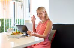 Happy young woman with tablet pc at restaurant Stock Image