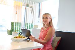 Happy young woman with tablet pc at restaurant Stock Images