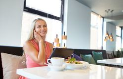 Happy young woman with tablet pc at restaurant Royalty Free Stock Image