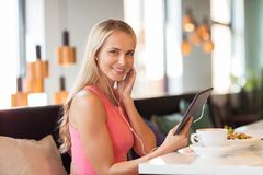 Happy young woman with tablet pc at restaurant Royalty Free Stock Photos