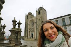 Happy young woman take selfie photo in front of Porto Cathedral in winter time. Self portrait of beautiful girl in Porto, Portugal.  stock image