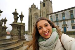 Happy young woman take selfie photo in front of Porto Cathedral in winter time. Self portrait of beautiful girl in Porto, Portugal.  royalty free stock image