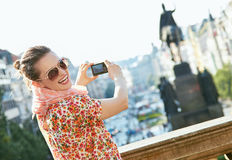 Happy young woman taking photos with digital camera in Prague Stock Image