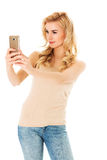 Happy young woman taking pictures of herself at smart phone Royalty Free Stock Image