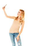 Happy young woman taking pictures of herself at smart phone Stock Photo