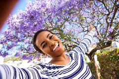 Happy young woman taking selfie by flowering tree Stock Images