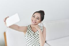 Happy young woman taking selfie with her cellphone while sitting at living room royalty free stock images