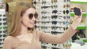 Happy young woman taking selfies while shopping for eyewear royalty free stock images