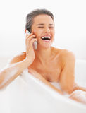 Happy young woman talking cell phone in bathtub Stock Photography