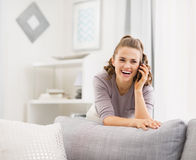 Happy young woman talking cell phone in living room Royalty Free Stock Image
