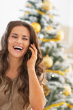 Happy young woman talking cell phone near christmas tree Royalty Free Stock Photos
