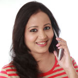 Happy young woman talking on cellphone against white background Royalty Free Stock Photos