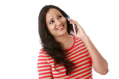 Happy young woman talking on cellphone against white Stock Images