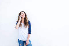 Happy young woman talking on cellphone by white wall Stock Photography