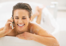 Happy young woman talking mobile phone while in bathtub Stock Images