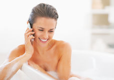 Happy young woman talking mobile phone in bathtub Stock Photo