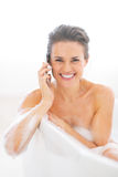 Happy young woman talking mobile phone in bathtub Royalty Free Stock Images