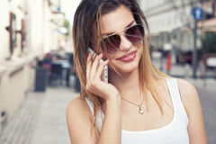 Happy young woman talking by mobile phone. Stock Photo