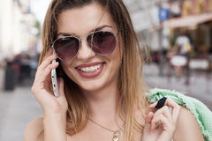 Happy young woman talking by mobile phone. Stock Photos