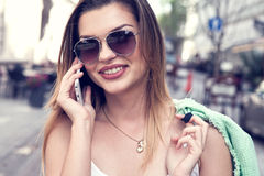 Happy young woman talking by mobile phone. Royalty Free Stock Image
