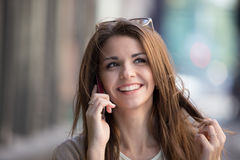 Happy young woman talking on mobile phone at city street lifestyle portrait. Royalty Free Stock Photos
