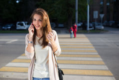 Happy young woman talking on mobile phone at city street lifestyle portrait. Stock Photos