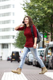 Happy young woman talking on mobile phone and crossing a road Royalty Free Stock Photography