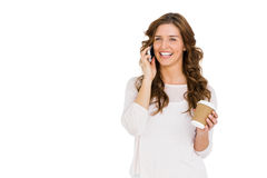 Happy young woman talking on mobile phone while having coffee. On white background Stock Photography