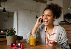 Happy young woman talking on mobile phone at home Stock Photography