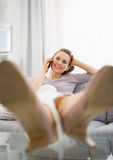 Happy young woman talking mobile phone in living room Stock Images