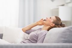 Happy young woman talking mobile phone while relaxing on couch Stock Photography