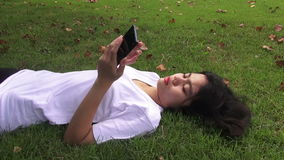 Happy young woman talking on mobile phone while sitting under a tree in autumnal park. HD Format : Happy young woman talking on mobile phone while sitting under stock video footage