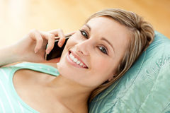 Happy young woman talking on phone lying on a sofa Royalty Free Stock Photo
