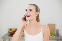 Happy young woman talking on smartphone. In the kitchen at home Stock Photo