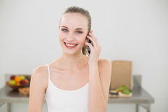 Happy young woman talking on smartphone smiling at camera. In the kitchen at home Royalty Free Stock Image