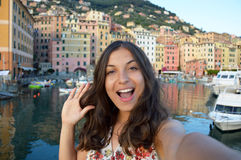 Happy young woman tanned taking selfie photo in a typical italian landscape with harbour and colorful houses for italian holidays. In Liguria, Italy Stock Photos