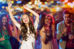 Happy young woman or teen dancing at disco club. People, party, holidays, night life and entertainment concept - happy young women or teen girl in fancy dress Stock Image