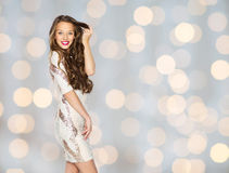 Happy young woman or teen in dress over lights Stock Photo
