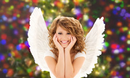 Happy young woman or teen girl with angel wings. People, holidays, christmas and party concept - happy young woman or teen girl with angel wings over lights Royalty Free Stock Photos