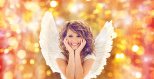 Happy young woman or teen girl with angel wings. People, holidays, christmas and party concept - happy young woman or teen girl with angel wings over lights royalty free stock photo