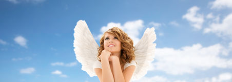 Happy young woman or teen girl with angel wings. People, holidays, christmas and religious concept - happy young woman or teen girl with angel wings over blue stock photography