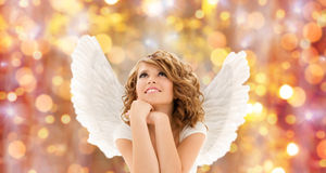 Happy young woman or teen girl with angel wings. People, holidays, christmas and religious concept - happy young woman or teen girl with angel wings over lights royalty free stock photos