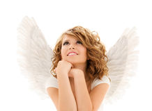 Happy young woman or teen girl with angel wings. People, holidays, christmas and religious concept - happy young woman or teen girl with angel wings over white Stock Image
