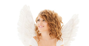 Happy young woman or teen girl with angel wings. People, holidays, christmas and religious concept - happy young woman or teen girl with angel wings over white Royalty Free Stock Images