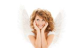 Happy young woman or teen girl with angel wings. People, holidays, christmas and religious concept - happy young woman or teen girl with angel wings over white royalty free stock photo