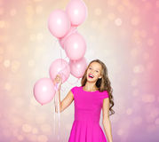 Happy young woman or teen girl with balloons. People, holidays, birthday and party concept - happy young woman or teen girl in pink dress with helium air Royalty Free Stock Photography