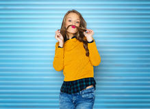 Happy young woman or teen girl in casual clothes. People, style and fashion concept - happy young woman or teen girl in casual clothes having fun making mustache Stock Photo