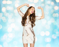 Happy young woman or teen girl in fancy dress. People, style, holidays and fashion concept - happy young woman or teen girl in fancy dress with sequins and long Stock Photos