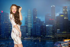 Happy young woman or teen girl over night city. People, holidays, hairstyle, nightlife and fashion concept - happy young woman or teen girl in fancy dress with Stock Image